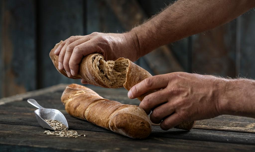 Bäckerhände brechen eine knusprige Brotstange - Bonnevit Feinbäckerei