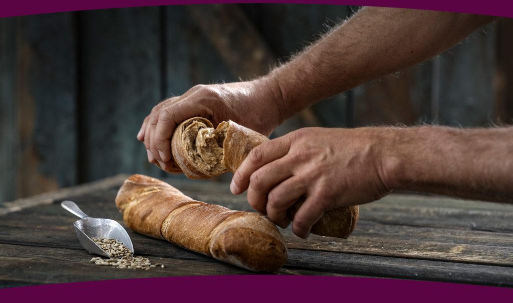 Männerhände brechen eine knusprige Brotstange - Bonnevit Feinbäckerei